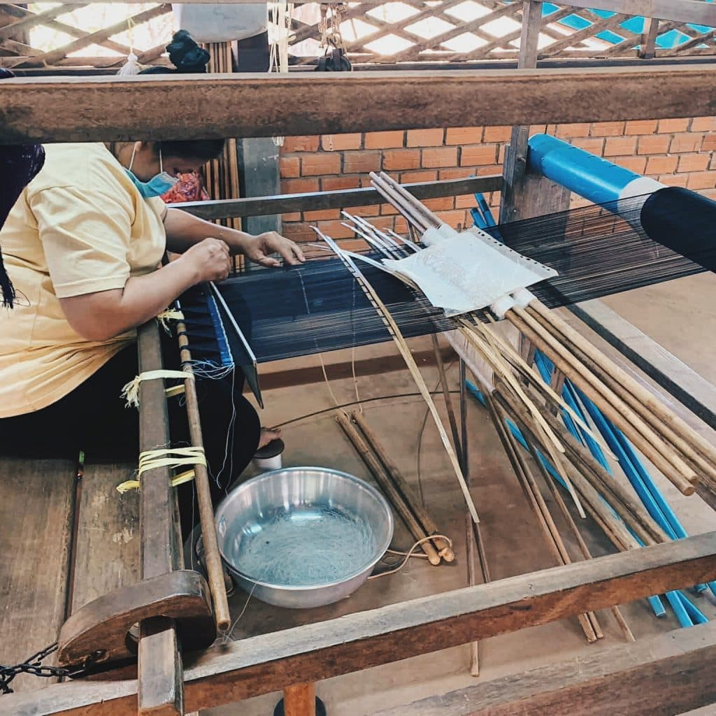 cambodian woman weaving at a traditional jenny
